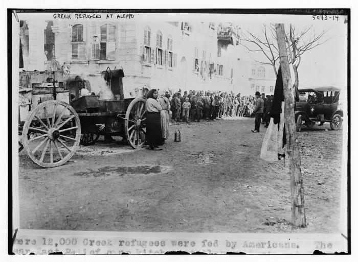 1923, Χαλέπι Συρίας, Έλληνες πρόσφυγες περιμένουν στη σειρά για το συσσίτιο. Στις 11 Ιουλίου η γαλλική κυβέρνηση, υπό τον έλεγχο της οποίας βρισκόταν η Συρία και ο Λίβανος, απαίτησε από την Ελλάδα να μεταφέρει με δικά της έξοδα και επιμελητεία, τουλάχιστον 2.000 πρόσφυγες στη Βηρυτό. Η ανθρωπιστική κρίση κορυφώθηκε όταν ο αμερικάνικος Ερυθρός Σταυρός, που αναφέρεται στη λεζάντα της φωτογραφίας ότι «σίτισε 12.000 Έλληνες», διέκοψε την παροχή βοήθειας την 1η Αυγούστου του 1923!
