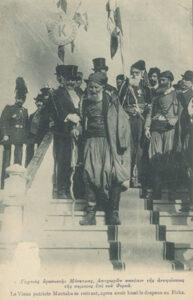 Διακρίνονται οι γηραιοί Κρήτες επαναστάτες Αναγνώστης Μάντακας και Χατζημιχάλης Γιάνναρης, στην τελετή ένταξης της Κρήτης στην Ελλάδα, φορώντας παραδοσιακό σπαστό φεσάκι με μαύρη φούντα